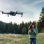 Frau steuert eine Drohne auf einer Waldlichtung
