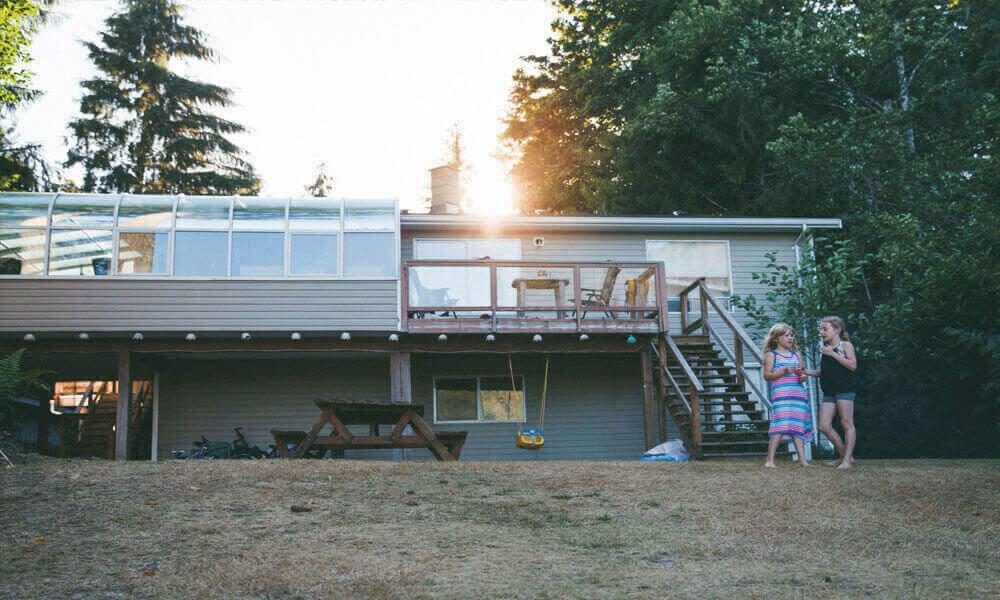 Zwei Mädchen stehen im Garten eines Ferienhauses im Wald