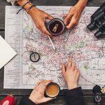Zwei Personen sitzen über einem Stadtplan und planen ihre Reise