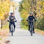 Zwei Menschen fahren mit ihrem E-Bike eine Allee entlang