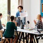 Eine Frau präsentiert in einem fünfköpfigen Team in einem Büro