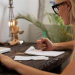 Frau sitzt am Schreibtisch, schreibt etwas auf und hat eine Hand in einem Portemonnaie