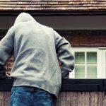 Person mit Kapuzenpulli steigt über einen Zaun auf ein Grundstück