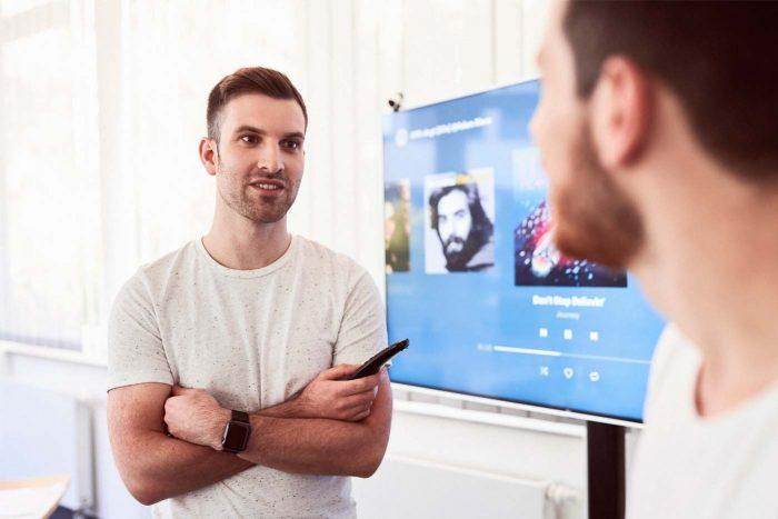 Ein Mann steht vor einem Bildschirm und spricht mit einem anderen Mann
