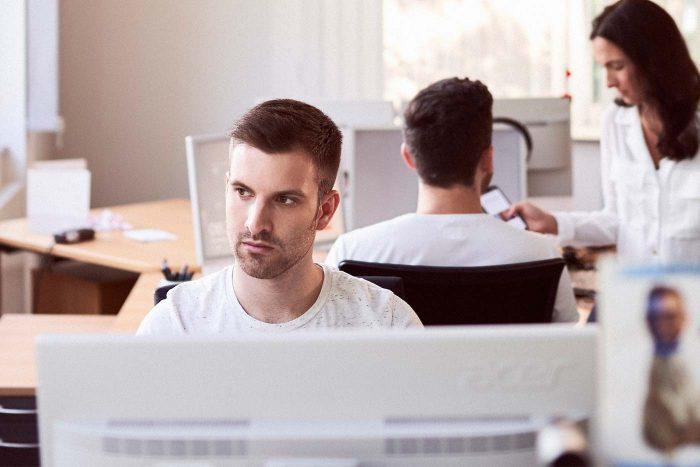 Mann arbeitet am PC, im Hintergrund sprechen ein Mann und eine Frau miteinander