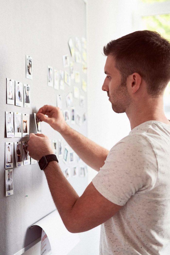 Mann pinnt Fotos an Pinnwand
