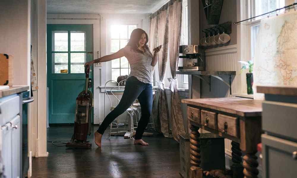 Frau tanzt in ihrer Küche, in der einen Hand ein Smartphone, in der anderen Hand einen Staubsauger