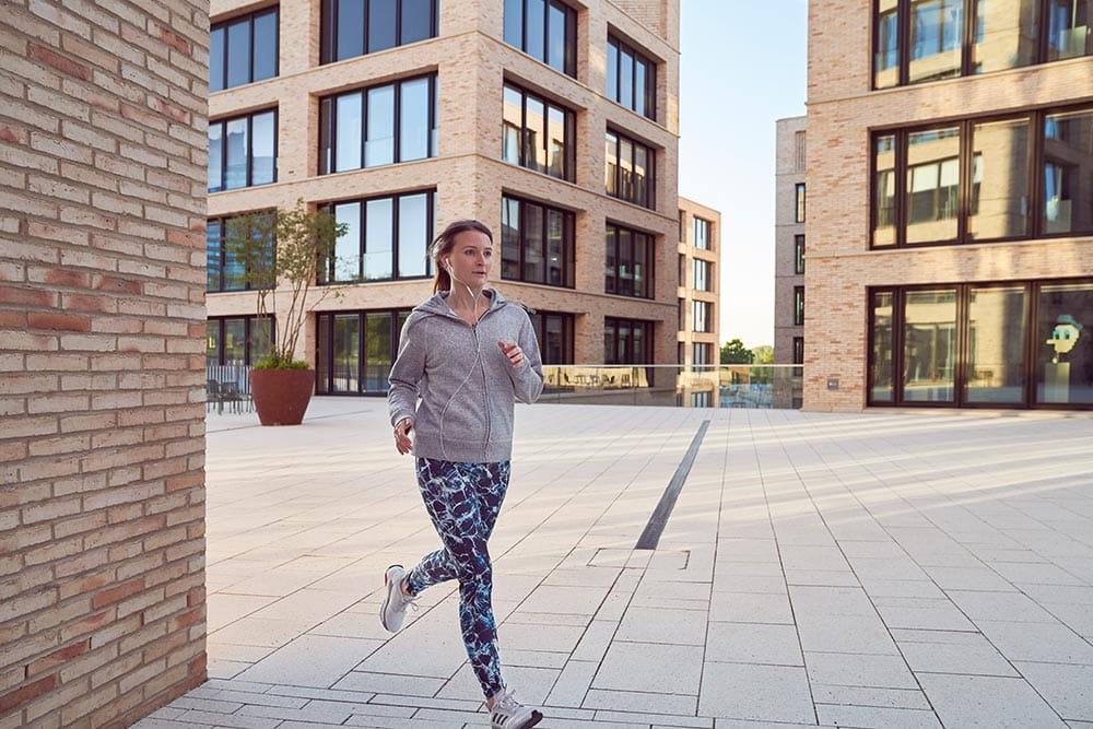 Frau joggt zwischen Bürogebäuden