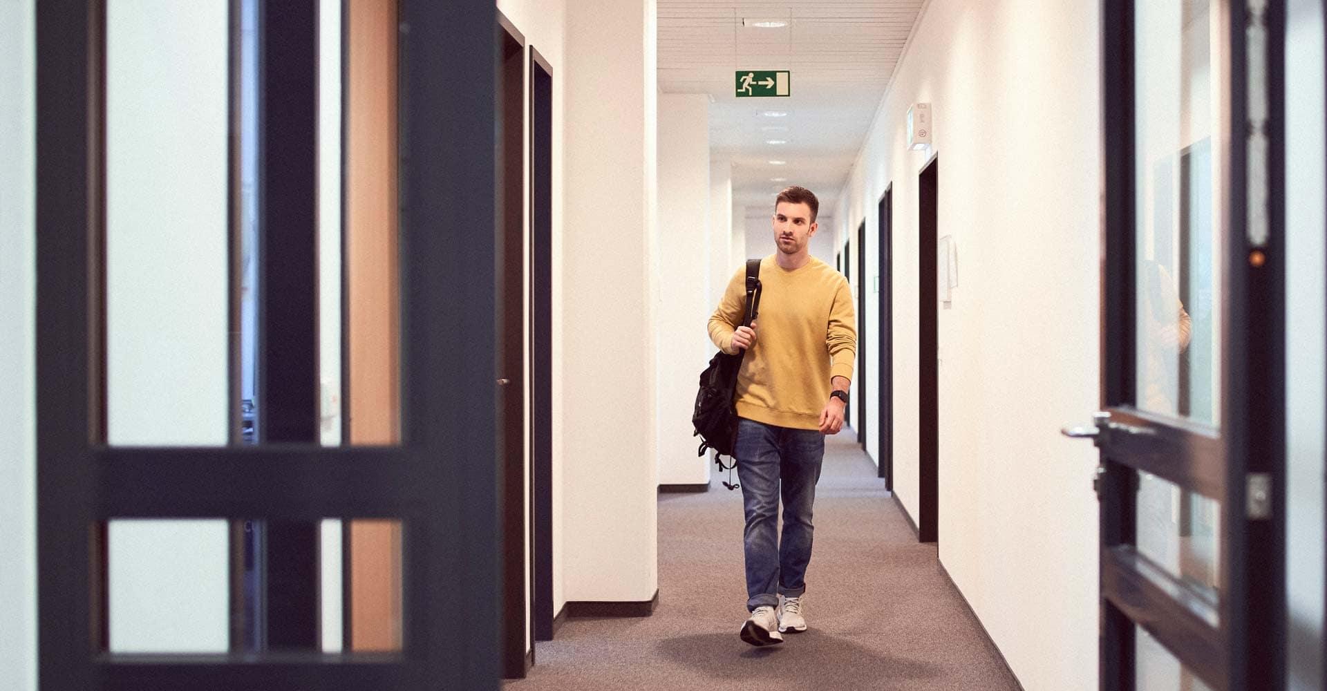 Mann geht einen Gang entlang