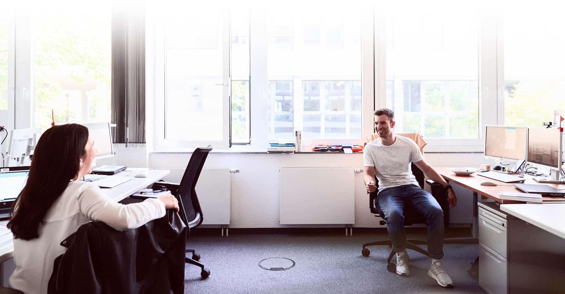 Mann und Frau unterhalten sich im Büro