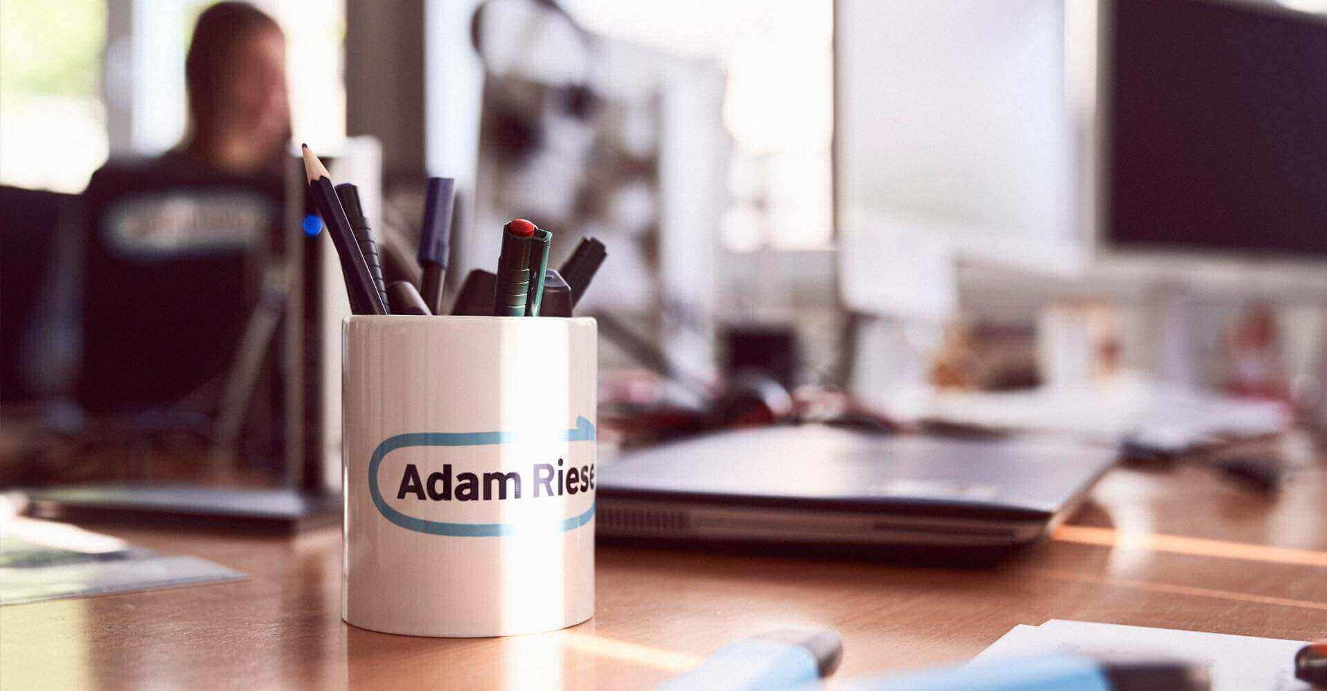 Tasse mit Stiften steht auf einem Schreibtisch