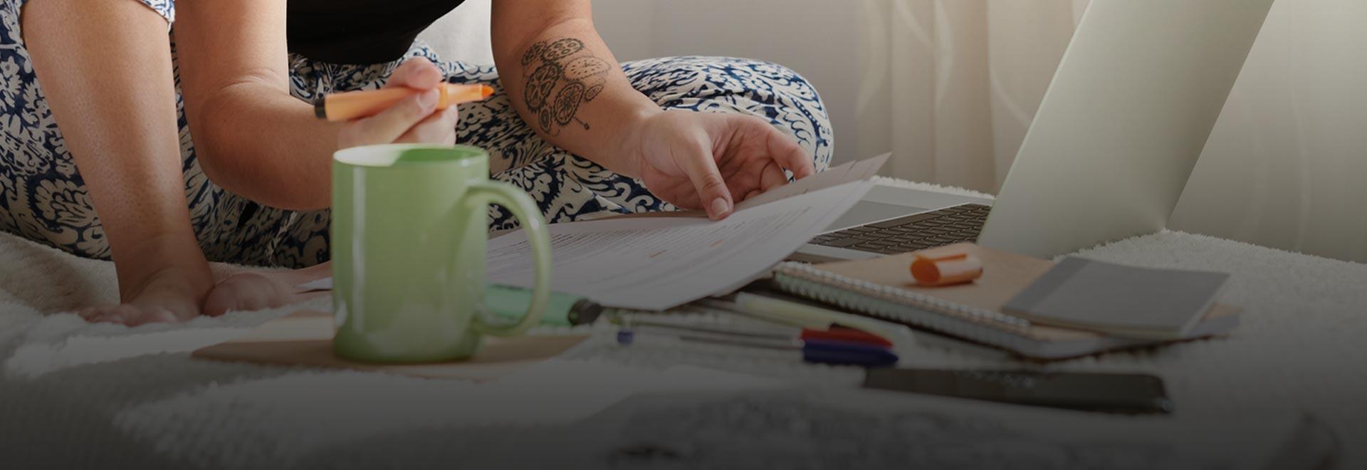 Eine Person sitzt mit Laptop und Dokumenten auf dem Bett.