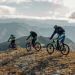 Drei Personen fahren mit den Mountainbikes über einen Berg, im Hintergrund eine Bergkette