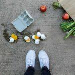 Eine Einkaufstüte ist heruntergefallen, es liegen Lebensmittel und zerbrochene Eier auf dem Boden.