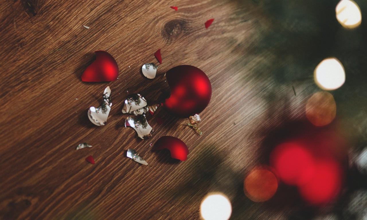 Zerbrochene Christbaumkugel auf Holzboden