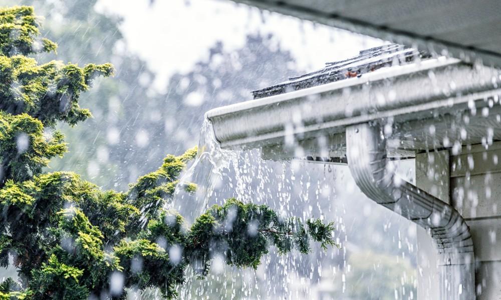 Starker Regen neben einer überlaufenden Dachrinne