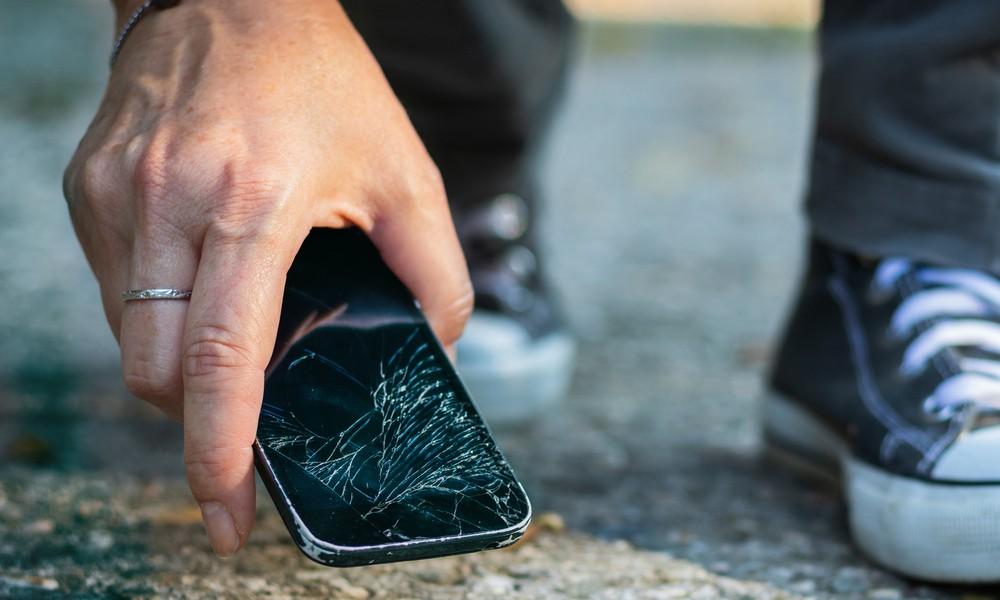 Jemand hebt ein auf den Asphalt gefallenes Smartphone auf. Das Display ist zersplittert.