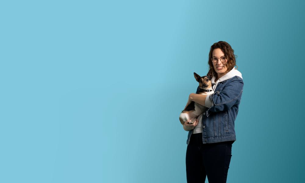 Junge Frau hält ihren Hund auf dem Arm