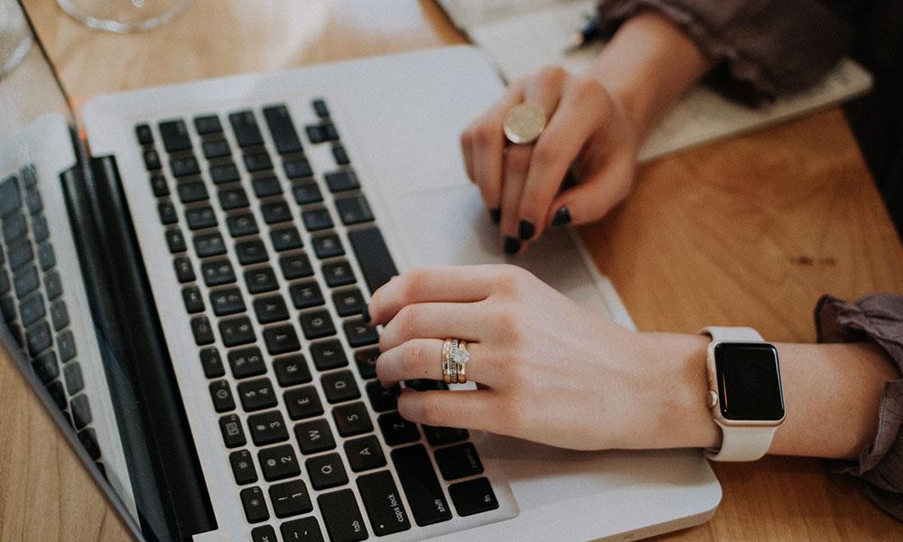 Zwei Hände tippen auf einem MacBook
